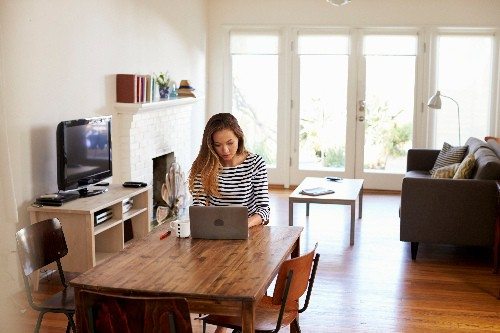 Woman working online at home at her kitchen table